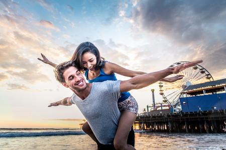 Paar liefhebbers op een romantische date op het strand bij zonsondergang Stockfoto