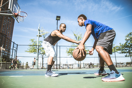 Two afroamerican athlethes playing basketball outdoors - Basketball athlete training on court in New York Фото со стока