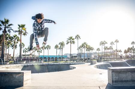 멋진 스케이트 보더 야외 - 그의 스케이트와 점프 및 트릭을 수행 Afroamerican 남자