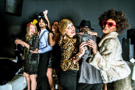 serpentinas: grupo multiétnico de amigos que celebran en un club nocturno - Clubbers que tiene partido Foto de archivo