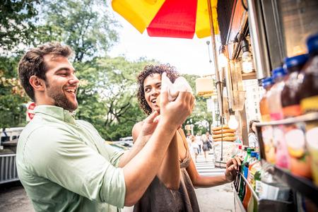 еда: Пара покупать хот-дог в киоске в Нью-Йорке Фото со стока