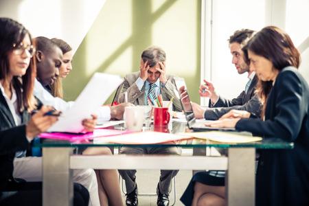 Zakenman met hoofdpijn tijdens een zakelijke bijeenkomst - Depressieve persoon met financiële problemen