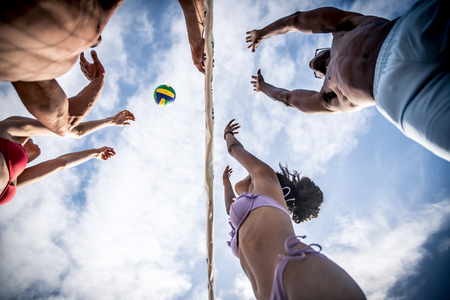 Group of friends playing beach volley on the beach. Stock Photo
