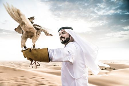 Árabe hombre con los emiratos tradicionales ropa caminando en el desierto con su pájaro halcón Foto de archivo