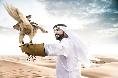 Arabic man with traditional emirates clothes walking in the desert with his falcon bird Imagens - 73348377