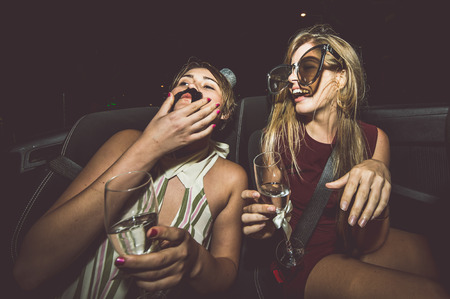 Party girls celebrate in Hollywood drinking champagne on a covertible car Reklamní fotografie