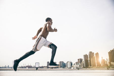 afroamerican: Sportive man training outdoors - Runner jogging, healthy lifestyle and sport concept