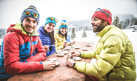 met: Group of friends talking and having fun in a outdoor restaurant on winter holidays - Snowboarders drinking hot coffee in a bar