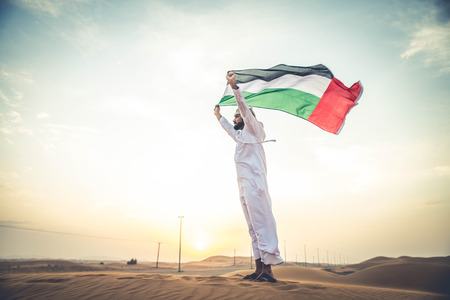 far away look: Arabian man walking  in the desert at sunrise