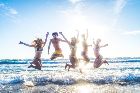 Multi-ethnic group of friends jumping on the beach - Young people having fun in the sea during summer holidays