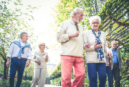 Group of senior people with some diseases walking outdoors - Mature group of friends spending time together Imagens
