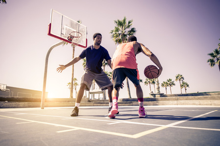 Friends playing basketball - Afro-american players having a friendly match outdoors photo