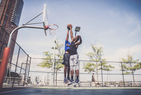 Two afroamerican athlethes playing basketball outdoors - Basketball athlete training on court in New York photo