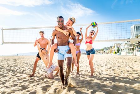 Groupe d'amis jouant au beach volley - Groupe multi-éthique de personnes ayant du plaisir sur la plage Banque d'images - 74296934