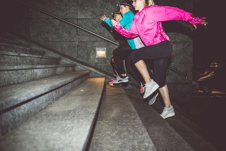 blinkers: Three women running in the night in the city center Stock Photo
