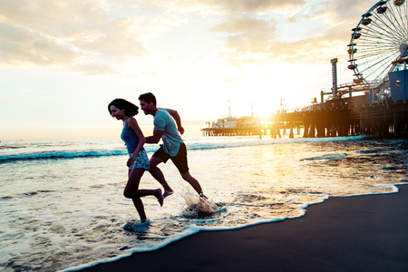 summertime: Couple of lovers on a romantic date at the beach at sunset Stock Photo