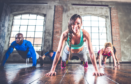 push people: Group of sportive people training in a gym - Multiracial group of athletes doing push ups