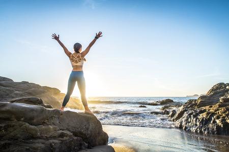 Opleiding van de vrouw yoga op het strand bij zonsondergang