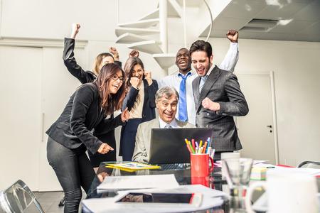 La gente de negocios en el trabajo en la oficina - reunión de negocios en una puesta en marcha, la gente mira el ordenador portátil y exultante