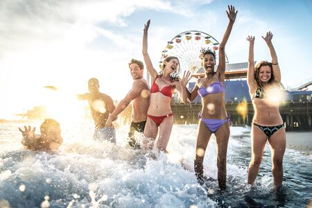 Group of friends splashing water while swimming in the sea - Multi-ethic group of people having fun on the beach Stock Photo