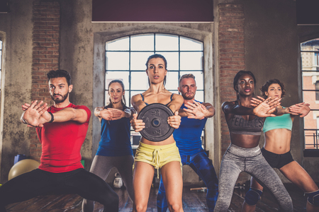 체육관에서 훈련하는 사람들을 쌓기를 그룹 - 개인 트레이너와 피트니스 클래스에서 낚시를 좋아하는 사람