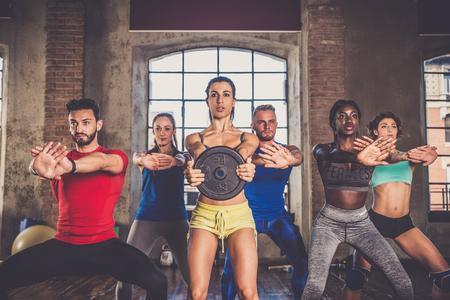 Multi-ethnische Gruppe von Menschen einer Ausbildung in einem Fitness-Studio - Personal Trainer und sportliche Personen in einer Fitness-Klasse Standard-Bild - 75180986