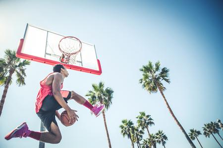 Basketball-Spieler, ein dunk - Sportive Mann, der draußen einen spektakulären dunk tun Standard-Bild - 75259225