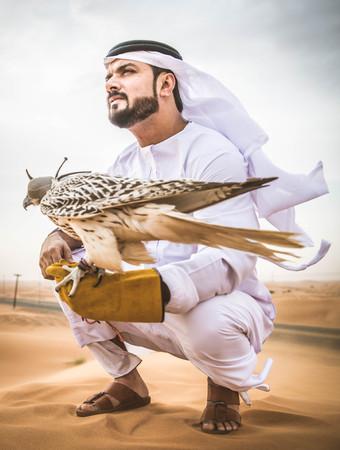 アラビア人が砂漠の日の出ウォーキング 写真素材