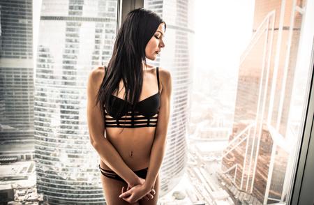 Mulher bonita olhando pela janela em seu belo apartamento Foto de archivo