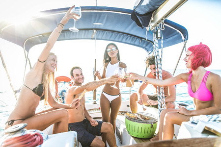 Multiethnic group of friends sailing on a boat - Summer holidays, young adults having fun Foto de archivo