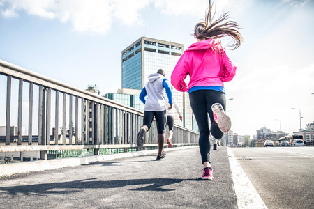 Three runners sprinting outdoors - Sportive people training in a urban area - healthy lifestyle and sport concepts Stock Photo
