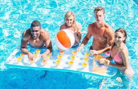 Multi-racial group of friends  having fun in a swimming pool Stock fotó