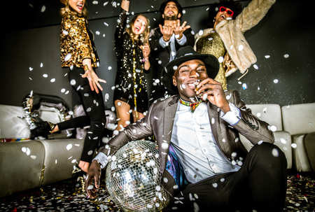 Multi-ethnic group of friends celebrating in a nightclub - Clubbers having party photo