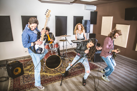 Rock band playing hard rock in the studio. Concept about entertainment and music
