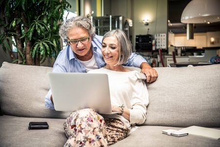 silver surfer: Senior Couple Using Laptop At Home Stock Photo