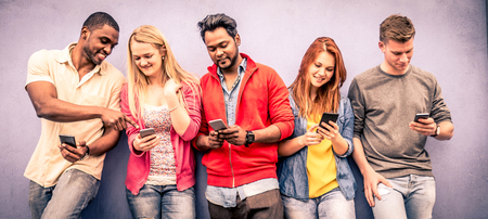 mania: Multiethnic group of friends looking down at phone and tablet - concepts about technology addiction and youth Stock Photo