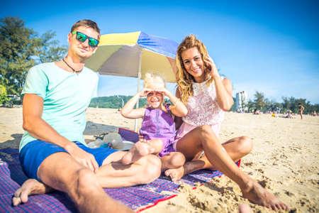 Happy playful family on a tropical beach photo
