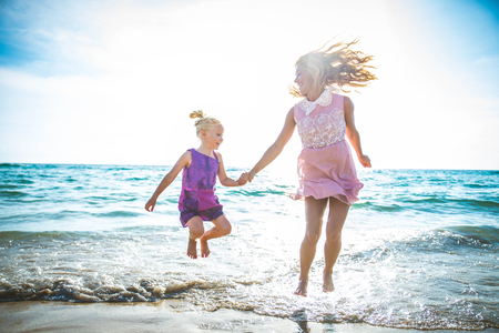 happy family mother and child daughter run laugh and play at beach photo
