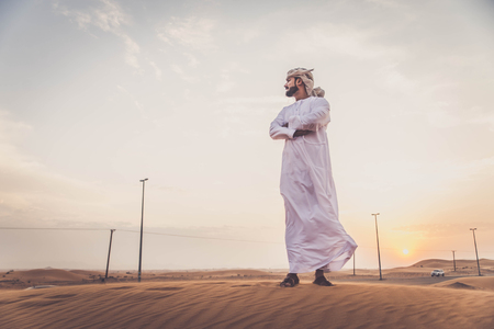 hombre arabe: Arabian man walking  in the desert at sunrise
