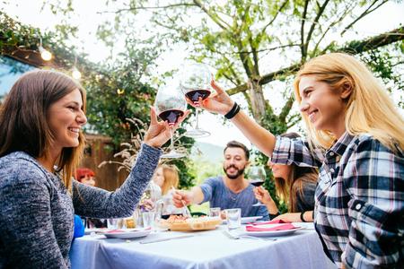 Grupo de amigos en el restaurante al aire libre - Las personas que tienen la cena en un jardín Foto de archivo - 79807964