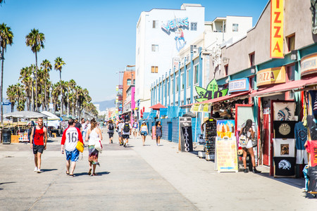 VENICE BEACH, USA - SEPTEMBER 29, 2016: The crowded Venice Beach Boardwalk. Lots of people are strolling down the boardwalk. On the sides there are several shops and palm trees.