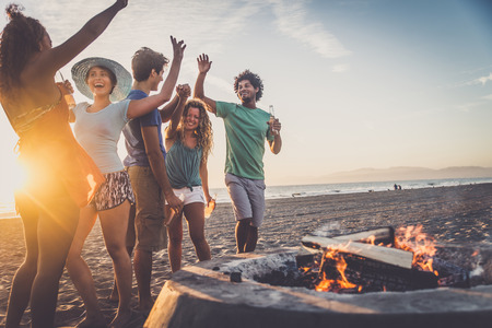 Multicultural group of friends partying on the beach - Young people celebrating during summer vacation, summertime and holidays concepts Foto de archivo