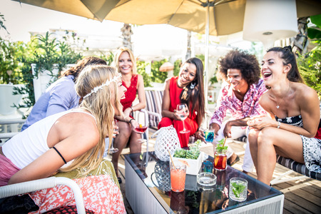 Multiethnic group of friends making party in a lounge bar - Cheerful young adults having fun and celebrating outdoors Stock Photo