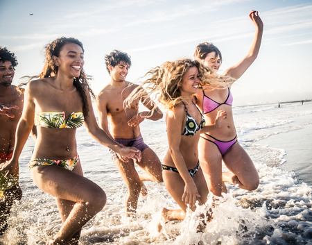 Multi-ethnic group of friends running on the beach - Young people having fun in the sea during summer holidays photo