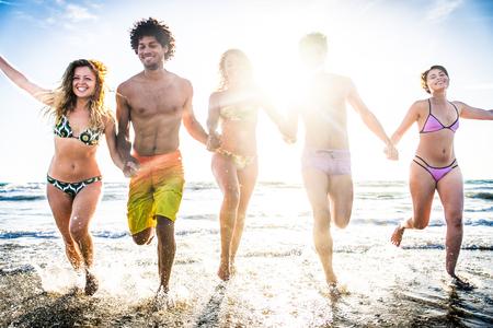 gruppo multi-etnico di amici in esecuzione sulla spiaggia - Giovani che hanno divertimento in mare durante le vacanze estive photo