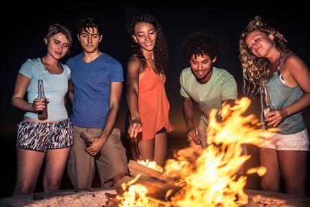 gruppo multiculturale di amici in festa sulla spiaggia - I giovani che celebrano durante le vacanze estive, estate e festivi concetti photo
