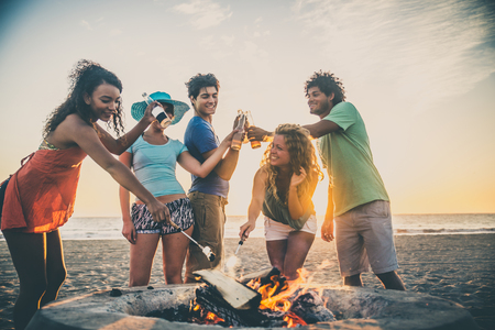 Multicultural group of friends partying on the beach - Young people celebrating during summer vacation, summertime and holidays concepts photo