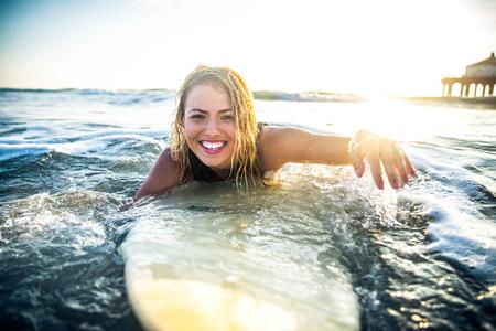 Vrouw surfen in de oceaan Stockfoto