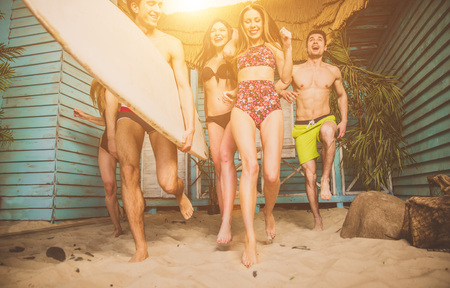 Group of five friends celebrating in their summer beach house