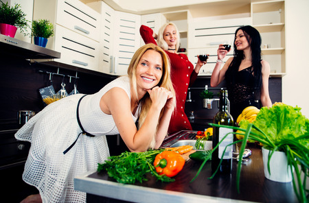 Three woman friends having fun in the kitchen and preparing food Stock Photo